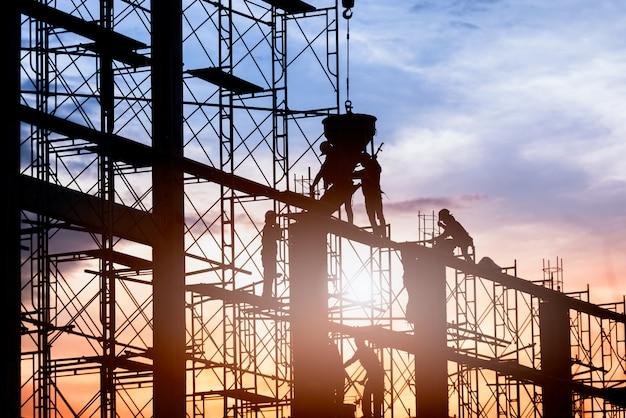 Sylwetka Pracownika Konstrukcja Odlewanie Betonu Prace Budowlane Na Rusztowaniach. Premium Zdjęcia