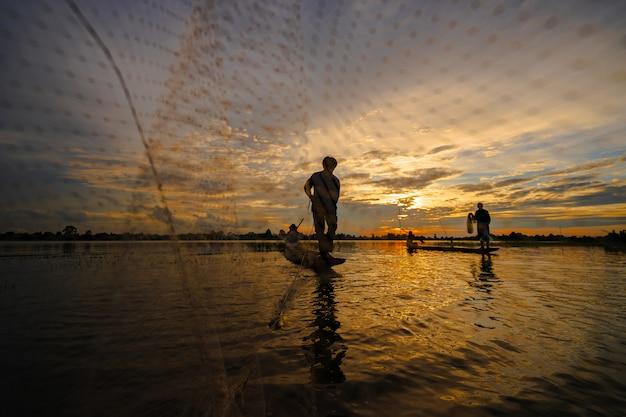 Sylwetka rybak na łodzi rybackiej z siecią na jeziorze przy zmierzchem, tajlandia Premium Zdjęcia