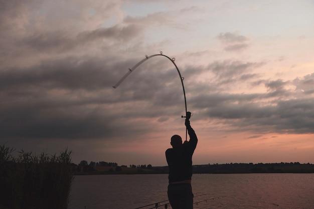 Sylwetka Rybak Rzuca Wędkę Do Jeziora O Zachodzie Słońca Premium Zdjęcia