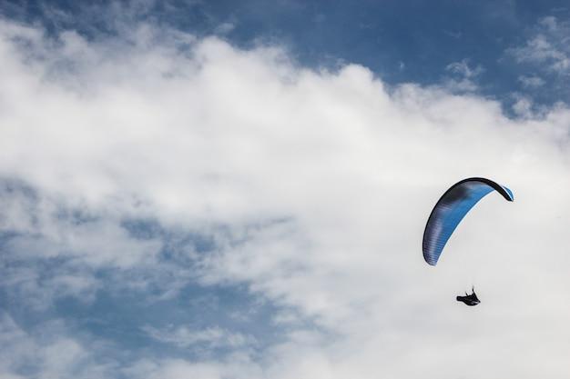 Sylwetka spadochron na niebieskim tle nieba Premium Zdjęcia