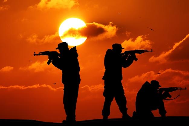 Sylwetka Trzy żołnierza Z Broniami Przy Zmierzchem Premium Zdjęcia
