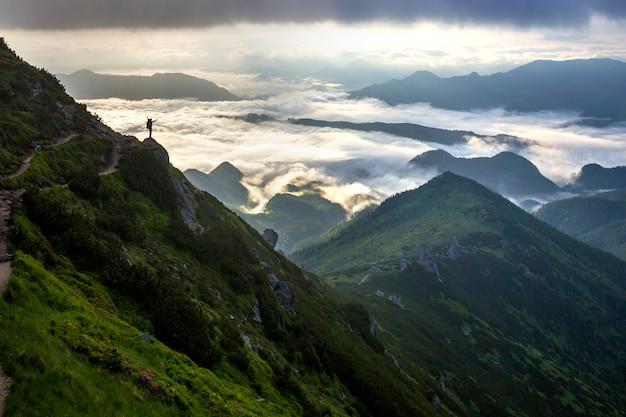Sylwetka Turysty Z Plecakiem Na Skalistym Zboczu Góry Z Podniesionymi Rękami Premium Zdjęcia