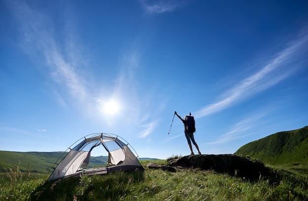 Sylwetka wycieczkowicz dziewczyna z plecakiem stojącym na szczycie wzgórza przeciw błękitne niebo, słońce i chmury w pobliżu namiotu, podnosząc ręce w powietrzu z kije trekkingowe w rękach, ciesząc się letni dzień Premium Zdjęcia