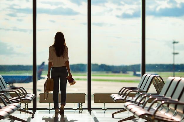 Sylwetka żeński linia lotnicza pasażer w lotniskowym holu czekaniu dla lota samolotu Premium Zdjęcia