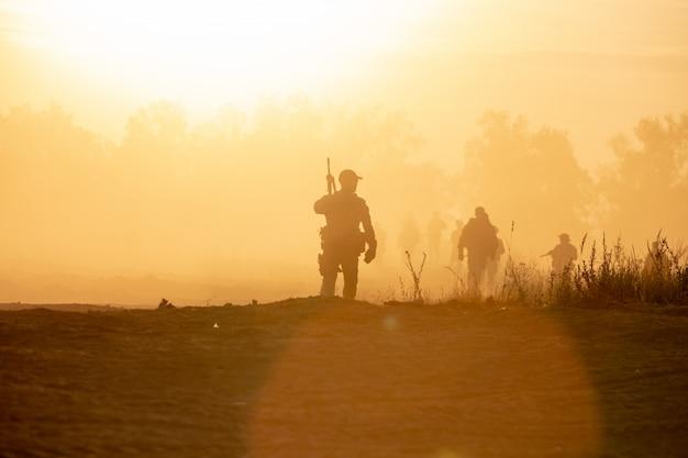 Sylwetka żołnierzy Akcji Chodzących Trzymających Broń To Dym I Zachód Słońca, A Balans Bieli To Efekt Ciemnej Sztuki Premium Zdjęcia