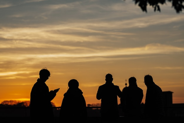 Sylwetki Ludzi Robiących Zdjęcia Zachodu Słońca Telefonami Komórkowymi I Kijem Do Selfie Na Zachodzie Słońca We Florencji We Włoszech. Premium Zdjęcia