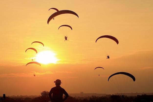 Sylwetki paramotor lub paratrike o zachodzie słońca Premium Zdjęcia