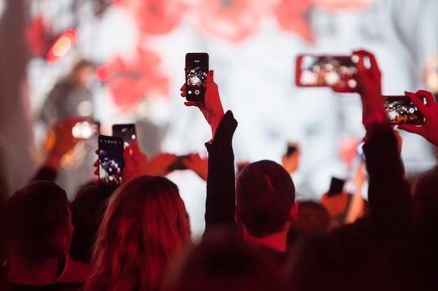 Sylwetki Tłumu Koncertowego Przed Jasnymi światłami Scenicznymi Premium Zdjęcia