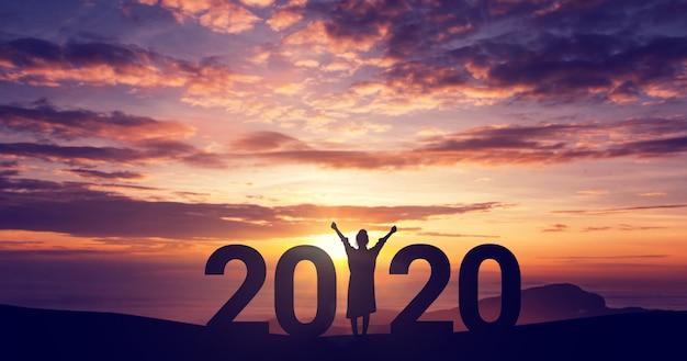 Sylwetki Wolności Młoda Kobieta Cieszy Się Na Wzgórzu I 2020 Rok Podczas Gdy świętujący Nowy Rok, Kopii Przestrzeń. Premium Zdjęcia