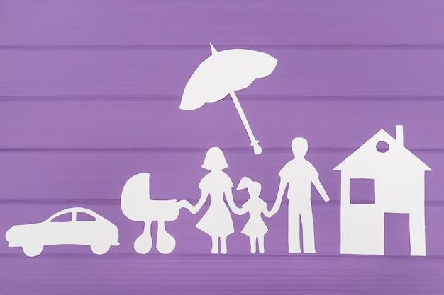 Sylwetki Wycięte Z Papieru Mężczyzny I Kobiety Z Dwiema Dziewczynami Pod Parasolem, W Pobliżu Domu I Samochodu Premium Zdjęcia