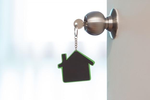 Symbol domu i trzymać klucz w dziurkę od klucza z miejsca na kopię Premium Zdjęcia