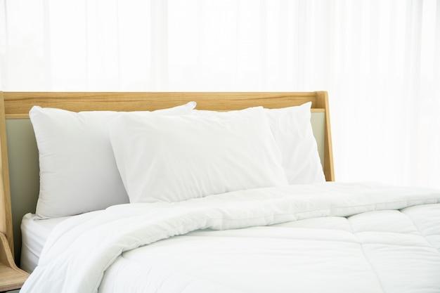 Sypialnia Urządzona W Minimalistycznym Stylu, Fotografia Białych Poduszek I Drewniane łóżko W Sypialni Z Naturalnym światłem Z Okna. Premium Zdjęcia