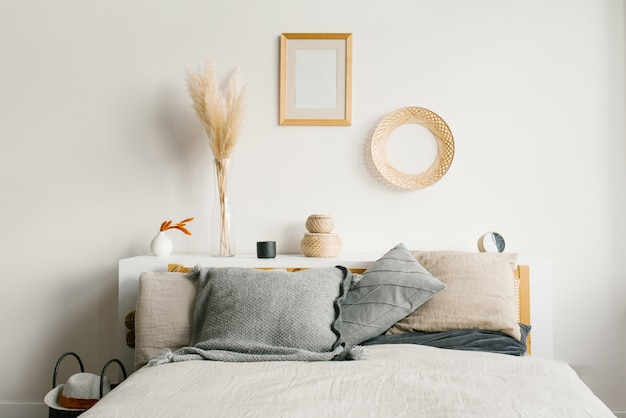Sypialnia W Skandynawskim Minimalistycznym Naturalnym Stylu. Szare Poduszki Na łóżku. Wystrój Nad łóżkiem Premium Zdjęcia