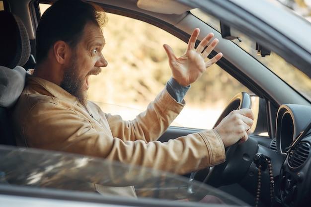 Szalony, Agresywny Kierowca Krzyczy Zirytowany Ruchem Drogowym Premium Zdjęcia