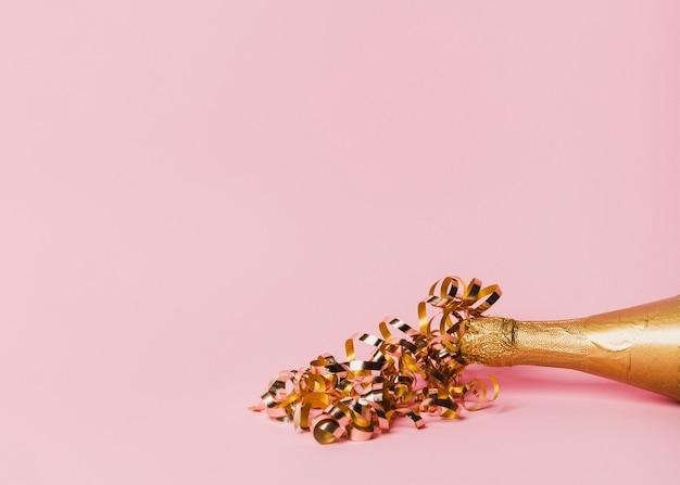 Szampańska butelka z faborkami i kopii przestrzeni różowym tłem Darmowe Zdjęcia