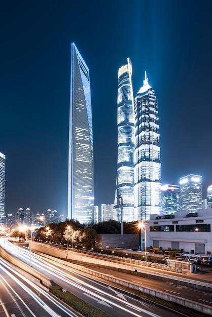 Szanghaj miasta budynki przy nocą i zamazanymi samochodowymi światłami Premium Zdjęcia