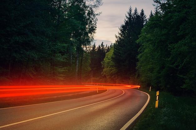 Szara Droga Asfaltowa Między Zielonymi Drzewami W Ciągu Dnia Z Czerwonymi światłami Ruchu Darmowe Zdjęcia
