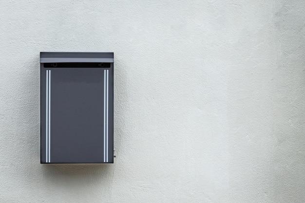 Szara metalowa skrzynka pocztowa zamontowana na ścianie cementowej Premium Zdjęcia