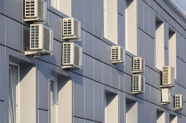 Szara ściana biurowca wykonana z metalowych płyt z oknami i klimatyzatorami Premium Zdjęcia
