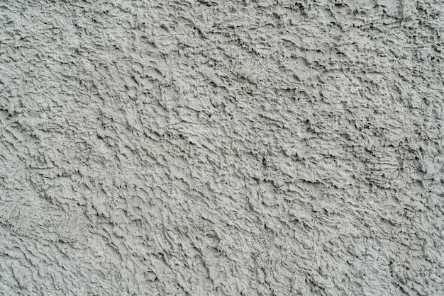 Szara tekstura nierównego tynku na ścianie domu. Premium Zdjęcia