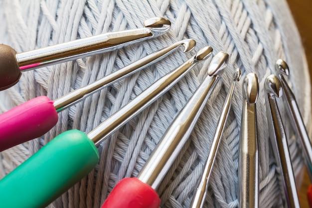 Szare przędze do szydełkowania i komplet wielobarwnych haczyków. Premium Zdjęcia