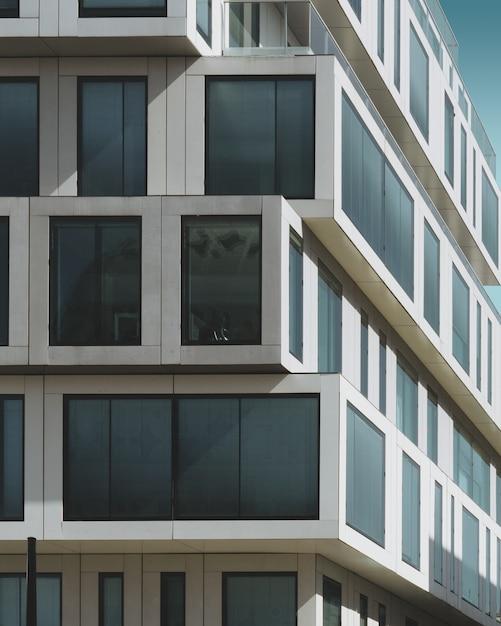 Szary Betonowy Budynek Z Dużymi Oknami Pod Niebieskim Niebem Darmowe Zdjęcia