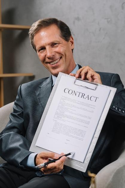 Szczęśliwy dojrzały prawnik wskazuje przy podpisu miejscem na kontrakcie dokumentuje z piórem Darmowe Zdjęcia