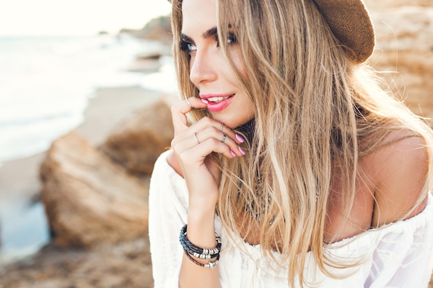 Szczegół Portret Atrakcyjna Blondynka Z Długimi Włosami Na Bezludnej Plaży. Trzyma Palec Na Ustach I Odwraca Wzrok. Darmowe Zdjęcia