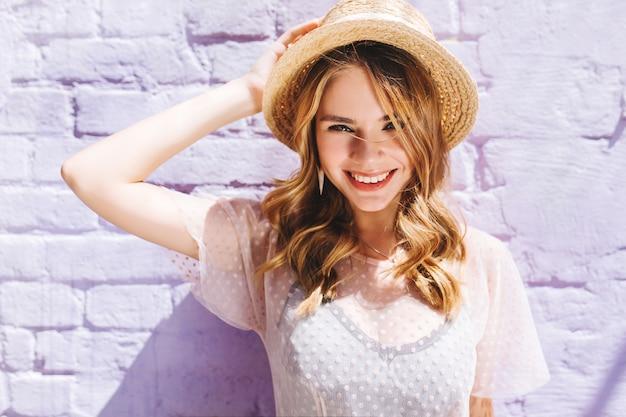 Szczegół Portret Błogiej Blondynki Pani Z Szerokim Uśmiechem Pozowanie W Słoneczny Dzień W Pobliżu Starej ściany Darmowe Zdjęcia