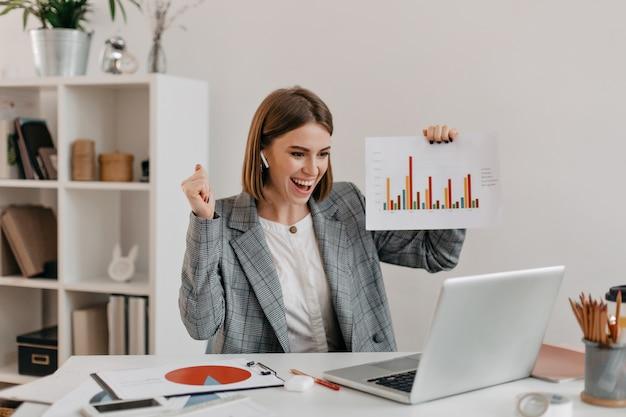 Szczegół Portret Kobiety Biznesu Szczęśliwy W Stylowym Stroju. Dziewczyna W świetnym Humorze Pokazuje Wykres Przez Skype. Darmowe Zdjęcia