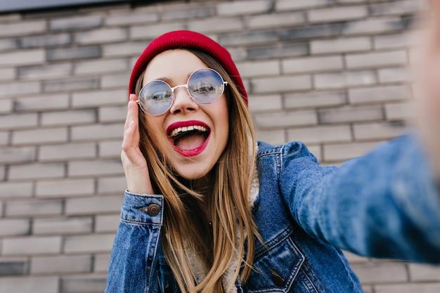 Szczegół Portret Oszałamiającej Blondynki W Dżinsowej Kurtce, Dzięki Czemu Selfie Z Uśmiechem. Zdjęcie Radosnej Białej Kobiety Z Wyrazem Szczęśliwej Twarzy Spędzającej Czas Na świeżym Powietrzu. Darmowe Zdjęcia