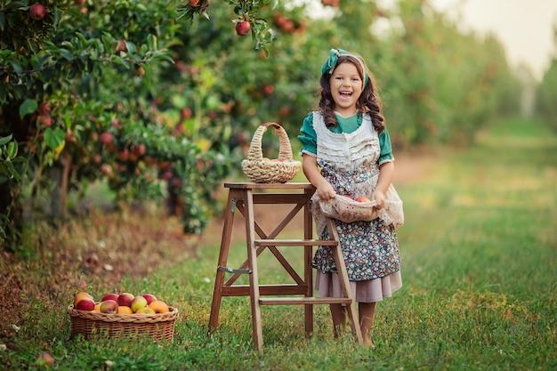 Szczegół Portret Pięknej ślicznej Dziewczyny O Ciemnych Włosach Z Czerwonym Jabłkiem W Dłoniach W Sadzie Jabłkowym Podczas żniw. Premium Zdjęcia