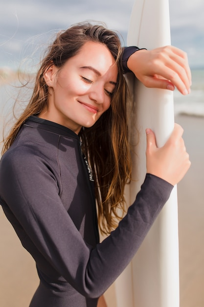 Szczegół Portret Szczęśliwa Uśmiechnięta Piękna Dziewczyna Z Długimi Włosami I Czarującym Uśmiechem Stoi W Słońcu Na Brzegu Oceanu I Zachowuje Spokój. Aktywna Sportowa Kobieta W Słoneczną Pogodę Z Deską Surfingową Darmowe Zdjęcia