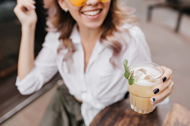 Szczegół Portret Uśmiechnięta Pani W Białej Koszuli Ręką Trzyma Szklankę Mrożonej Kawy Na Pierwszym Planie Darmowe Zdjęcia