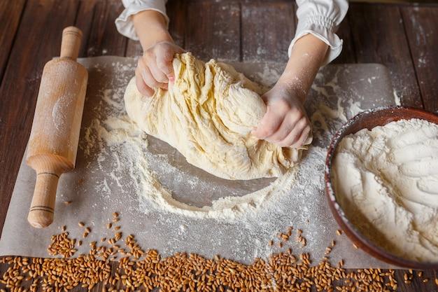 Szczegół ręce ugniata ciasto Premium Zdjęcia