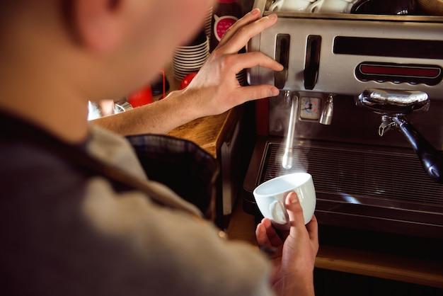 Szczegóły przygotowywa świeżą kawę espresso na przemysłowej browarnianej maszynerii barista. Premium Zdjęcia