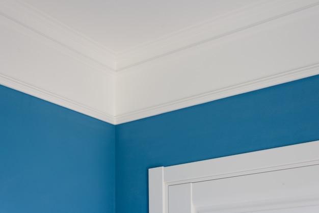 Szczegóły we wnętrzu. listwy sufitowe, ściany pomalowane na niebiesko, białe drzwi Premium Zdjęcia
