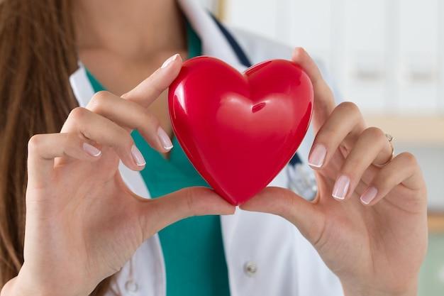 Szczelnie-do Góry Kobiece Lekarz Trzymając Się Za Ręce Czytać Serce. Opieka Zdrowotna, Kardiologia I Koncepcja Medyczna Premium Zdjęcia