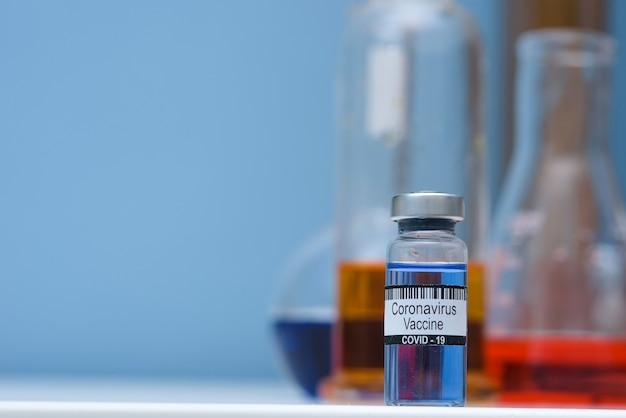 Szczepionka Przeciwko Koronawirusowi W Butelce Do Wstrzykiwań Na Stole Na Tle Laboratorium Medycznego, Miejsce Na Tekst. Pokonanie Epidemii Koronawirusa Sars-cov-2. Premium Zdjęcia