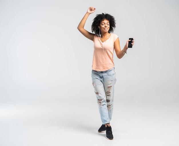 Szczęśliwa Afrykańska Kobieta Z Afro I Ubranie, Taniec Do Muzyki, Której Słucha Ze Swojego Telefonu. Premium Zdjęcia
