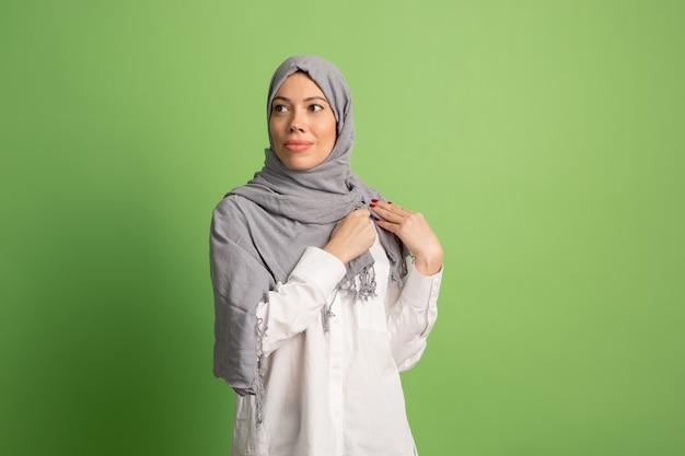Szczęśliwa Arabka W Hidżabie. Portret Uśmiechnięta Dziewczyna, Stwarzających Na Zielonym Tle Studio. Darmowe Zdjęcia