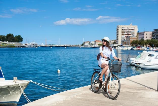 Szczęśliwa Atrakcyjna Dziewczyna W Okularach Przeciwsłonecznych Iz Plecakiem Jedzie Na Rowerze Wzdłuż Kamienistego Chodnika Premium Zdjęcia