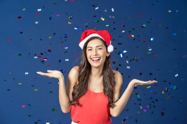 Szczęśliwa Atrakcyjna Kobieta Azji świętować Imprezę Z Multi Kolor Konfetti Na Niebieskim Tle Premium Zdjęcia