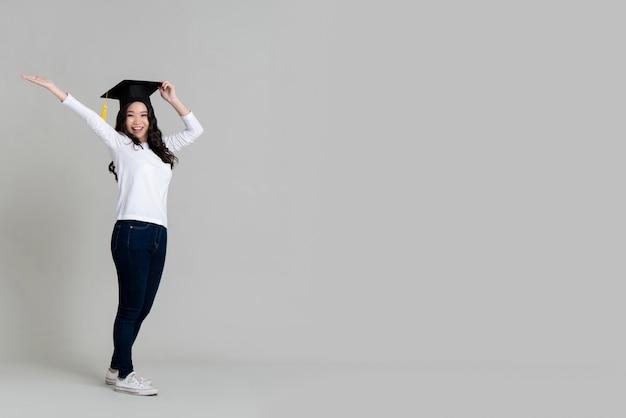 Szczęśliwa azjatycka kobieta uśmiecha się skalowaną nakrętkę i jest ubranym Premium Zdjęcia