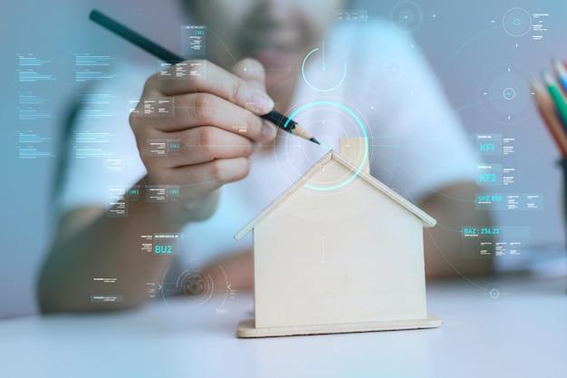Szczęśliwa azjatycka kobieta używa ołówek rysować z drewnianym domowym prosiątkiem bankiem i cyber technologią Premium Zdjęcia