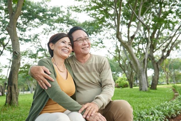 Szczęśliwa Azjatycka Para Na Daktylowym Obsiadaniu Na ławce W Parku Patrzeje Daleko Od Darmowe Zdjęcia