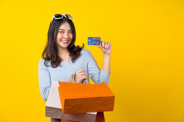 Szczęśliwa Azjatycka Uśmiechnięta Kobieta Przedstawia Kredytową Kartę I Niesie Zakupy Coloful Torbę Dla Przedstawiać Online Zakupy Na Odosobnionej Kolor żółty ścianie Premium Zdjęcia