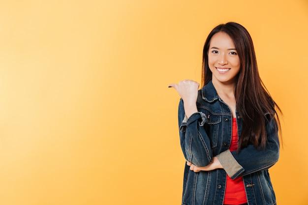 Szczęśliwa Azjatykcia Kobieta Wskazuje Daleko Od Na Copyspace W Drelichowej Kurtce Darmowe Zdjęcia