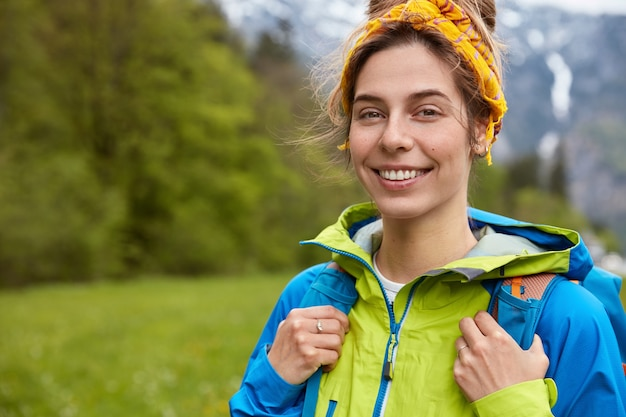 Szczęśliwa Beztroska Młoda Kobieta Pozuje Na Górskim Wzgórzu, Uśmiecha Się Do Kamery Darmowe Zdjęcia