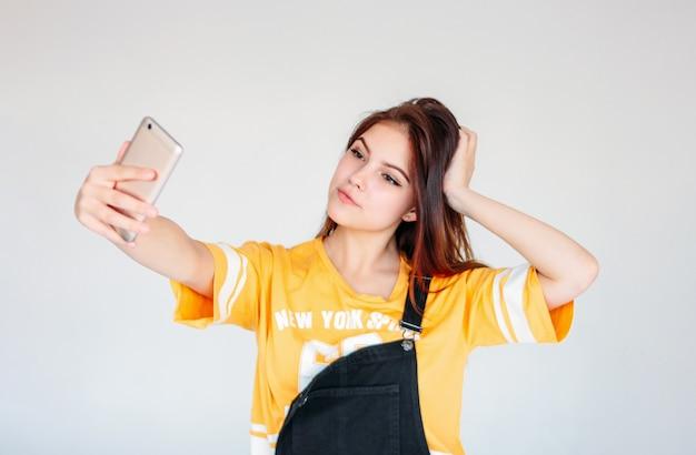 Szczęśliwa Beztroska Uśmiechnięta Nastolatek Dziewczyna Z Ciemnymi Długimi Włosami W żółtej Koszulce Robi Selfie Premium Zdjęcia